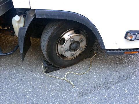 引越しトラックのタイヤに輪留めをした様子