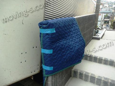 引越しトラック荷台の扉が万が一塀にぶつかる事を想定し、塀を養生します