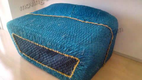 ソファをキルティング素材の梱包材で梱包した様子