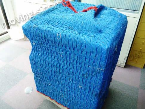 コピー機をキルティング素材の梱包材で梱包した様子